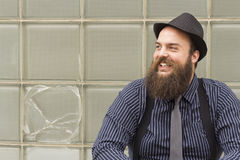 Snazzy Bearded Man. Stylish bearded man laughs with delight by broken window Royalty Free Stock Photos