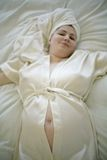 Sneak peek. Pregnant woman wearing light silk bathrobe and towel around head, lying in bed with bared belly button Stock Image