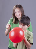 Sneak up and pop the balloon. Older sister going to pop her little brother's balloon royalty free stock photos