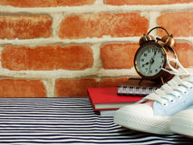 Sneaker and alarm clock with notebook and diary with space copy Stock Photos