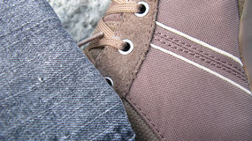 Sneaker and denim. Closeup of sneaker, laces and denim jeans royalty free stock photography