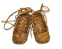 Sneaker wood woven birch sandals for everyday wear in the village on a wooden background Stock Images