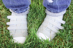 Sneakers. Person with long jeans wears  sneakers, and is standing on grass Royalty Free Stock Photo