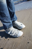 Sneakers. Person with long jeans wears  sneakers, and is standing on Stock Images