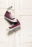 Sneakers. Red checkered sneakers hanging on door knob Royalty Free Stock Image