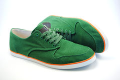Sneakers. Green sneakers with orange line on white background Stock Photos