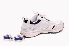 Sneakers. One large sneaker followed by two very tiny sneakers Royalty Free Stock Images