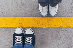 Sneakers from above. Male and female feet in sneakers from above, standing at dividing line Royalty Free Stock Photography