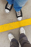 Sneakers from above. Male and female feet in sneakers from above, standing at dividing line Stock Images