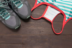 Sneakers and activewear are on the wooden background Stock Photo
