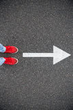 Sneakers on the asphalt road with drawn direction arrow Royalty Free Stock Image