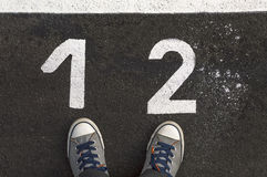 Sneakers on asphalt road with 1 and 2 number royalty free stock photos