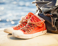 Sneakers and backpack on seascape Stock Images