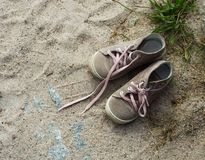 Sneakers on a beach. A pair of sneakers on a beach stock photo