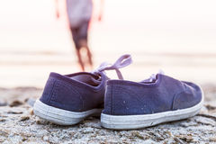 Sneakers at the beach with running boy Stock Photo