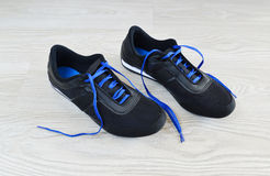 Sneakers with blue laces are on  floor Stock Photography