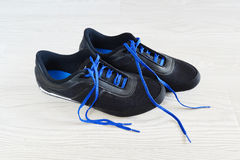 Sneakers with blue laces are on  floor Royalty Free Stock Photo