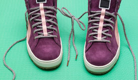sneakers and bow fron strings on green background Stock Image