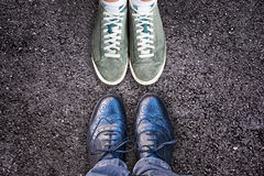 Sneakers and business shoes face to face on asphalt, work life balance concept Royalty Free Stock Image