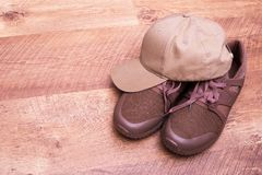Sneakers and cap on laminate. Summer men`s shoes and hat. Place for text near clothes stock photo