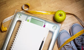 Sneakers, centimeter, green apple, notebook, scale. Healthy lifestyle concept. Sneakers, green apple and scale. Weight loss,  healthy lifestyle concept Royalty Free Stock Image