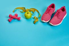 Sneakers, centimeter, green apple, weight loss, running, healthy. Eating, healthy lifestyle concept on a blue background. Top view. Copy space. Still life. Flat Royalty Free Stock Image