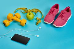 Sneakers, centimeter, green apple, weight loss, running, healthy eating, healthy lifestyle concept. On a blue background. Top view. Copy space. Still life. Flat Royalty Free Stock Images
