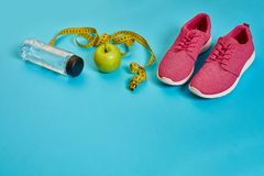 Sneakers, centimeter, green apple, weight loss, running, healthy eating, healthy lifestyle concept. On a blue background. Top view. Copy space. Still life. Flat Stock Photo