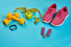 Sneakers, centimeter, green apple, weight loss, running, healthy. Eating, healthy lifestyle concept on a blue background. Top view. Copy space. Still life. Flat Stock Photography