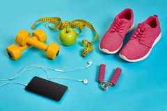 Sneakers, centimeter, green apple, weight loss, running, healthy. Eating, healthy lifestyle concept on a blue background. Top view. Copy space. Still life. Flat Stock Image