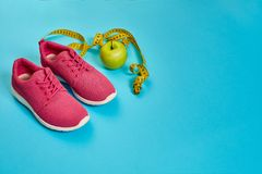 Sneakers, centimeter, green apple, weight loss, running, healthy. Eating, healthy lifestyle concept on a blue background. Top view. Copy space. Still life. Flat Royalty Free Stock Images
