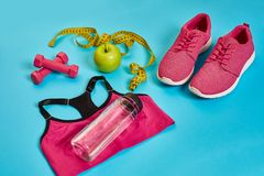 Sneakers, centimeter, green apple, weight loss, running, healthy. Eating, healthy lifestyle concept on a blue background. Top view. Copy space. Still life. Flat Royalty Free Stock Photography