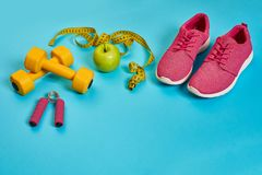 Sneakers, centimeter, green apple, weight loss, running, healthy. Eating, healthy lifestyle concept on a blue background. Top view. Copy space. Still life. Flat Stock Photo