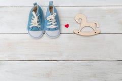Sneakers dla zabawkarskiego drewnianego konia na drewnianym tle i dzieciaka Fotografia Royalty Free