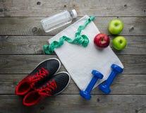 Sneakers dumbbells butelka wodny jabłko i miara taśmy obraz stock