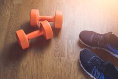 Sneakers and dumbbells fitness on a wooden background. Royalty Free Stock Photography