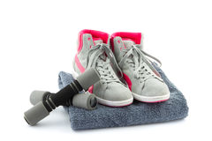 Sneakers with dumbbells and towel Royalty Free Stock Photos