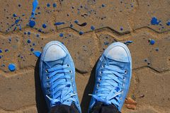 Sneakers, explore the world concept. Sneakers from an aerial view on concrete block pavement. Top view royalty free stock photo