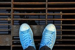 Sneakers, explore the world concept. Sneakers from an aerial view on steel sewer cover. Top view stock image
