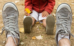 Sneakers of father sitting on field with his son. Sneakers front view of men sitting on field and back view of child´s snakers soles with a tree leaf in hand Royalty Free Stock Image