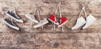 Sneakers on the floor. Four pairs of sneakers hang on a nail on a wooden fence background Royalty Free Stock Photo