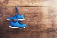 Sneakers on the floor. Pair of sneakers hang on a nail on a wooden fence background Stock Photos