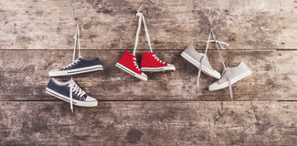 Sneakers on the floor. Three pairs of sneakers hang on a nail on a wooden fence background Royalty Free Stock Photography