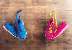 Sneakers on the floor. Two pairs of sneakers hang on a nail on a wooden fence background Royalty Free Stock Photography