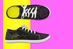 Sneakers with floral pattern in bright multi-colored background. Stock Image
