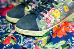 Sneakers with floral print on the background of women`s shirt with bright colors royalty free stock image