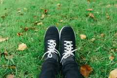 Sneakers on girl legs on grass during sunny serene summer day. Stock Photo