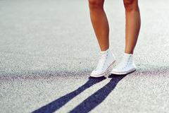 Sneakers on girl. Young woman legs. Outdoors Stock Photo
