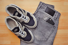 Sneakers with gray jeans on wooden background Stock Photo