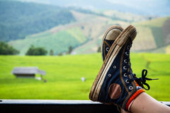 Sneakers with green fields in the valley. Royalty Free Stock Photography